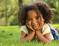 Smiling little girl relaxing in the grass with her chin on her hands