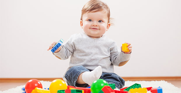 Twinkle-eyed baby sits on rug amid a pile of colorful toys and blocks