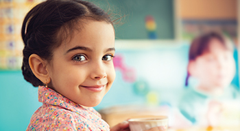 Young girl in a classroom setting smiles at camera